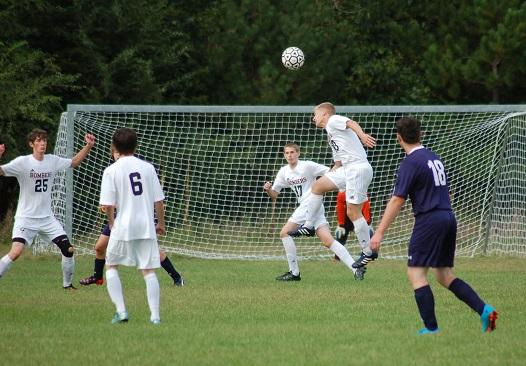 A Cannon Falls defender heads the ball away