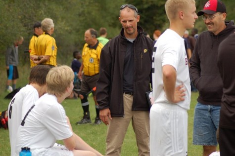 Coach Rueger chats with team members on the sideline