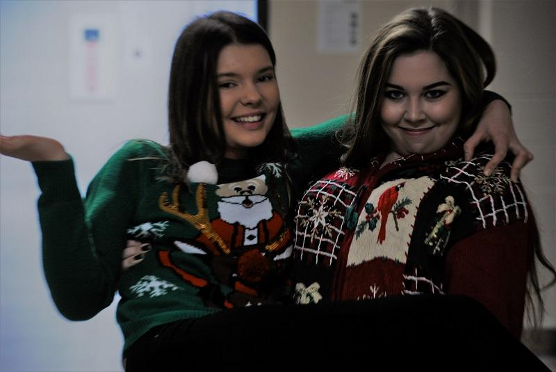 Two+seniors+pose+for+their+final+Ugly+Sweater+dress+up+day.