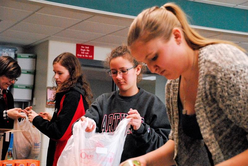 NHS students pack backpacks with food