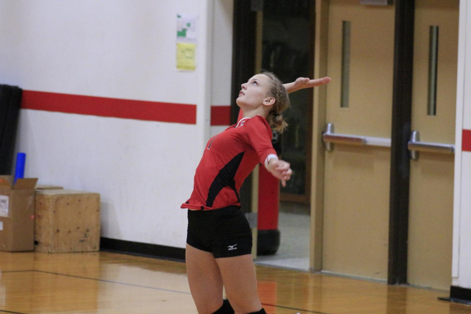 Senior Tatum Pickar serving during a game.
