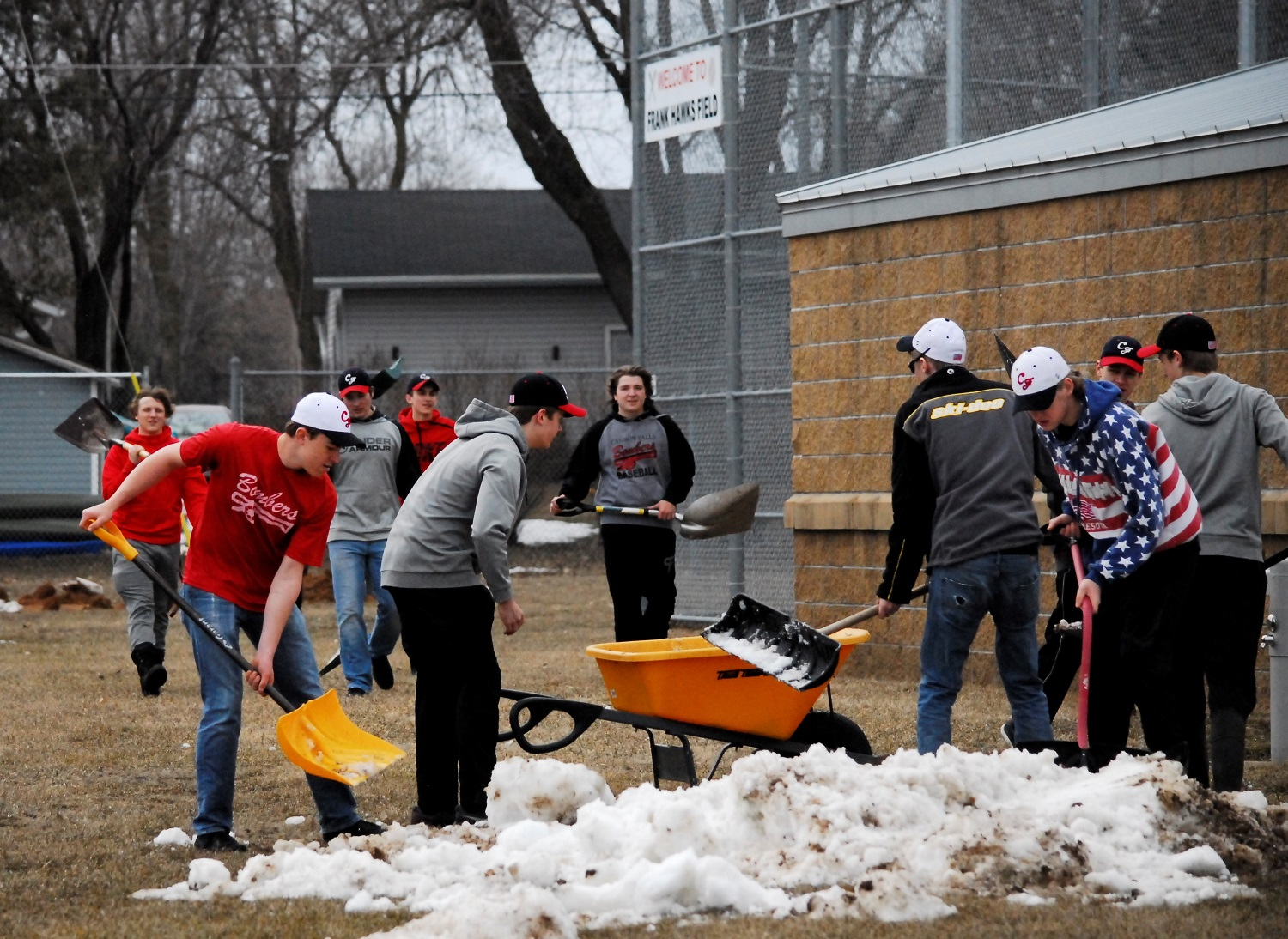 The boys of the baseball team shovel snow off of the field before their upcoming game.