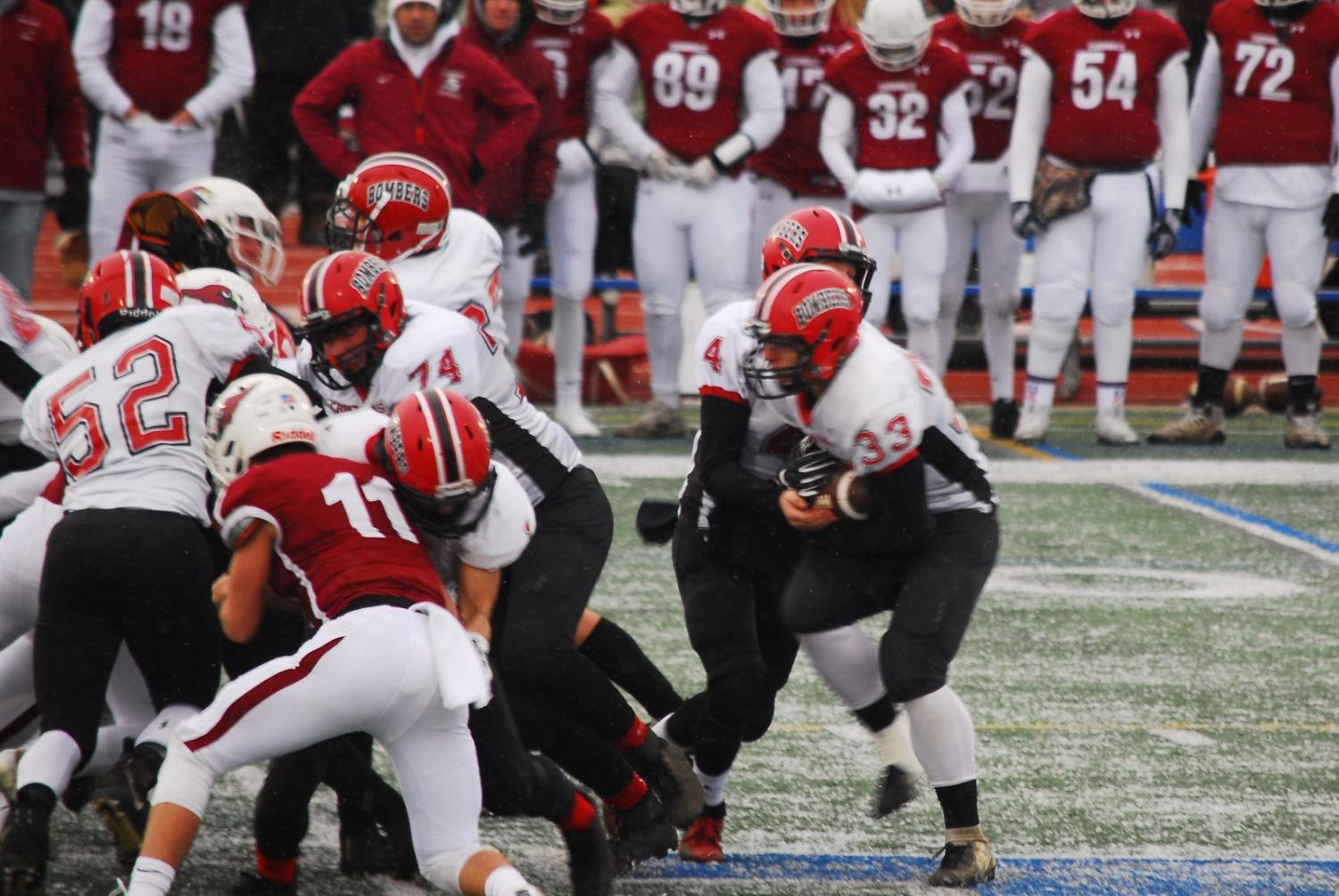 Bomber running back Logan Hofstedt crashes the line in a snowy state tournament game.