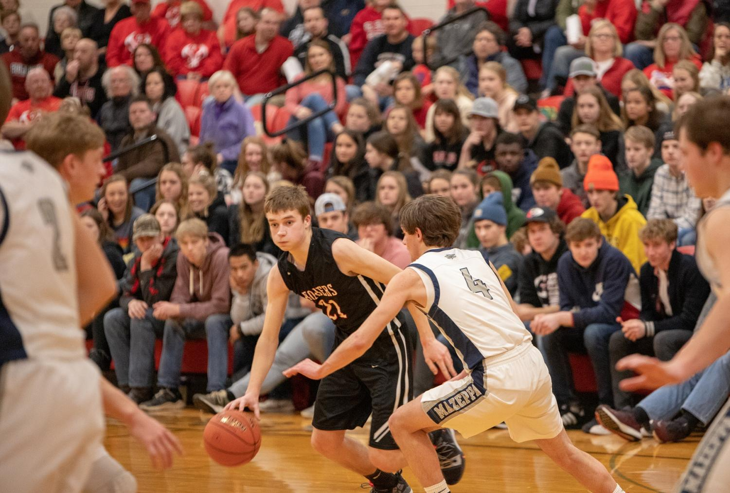Senior, Luke Sjoquist dodges his opponent and drives to the basket for a layup.