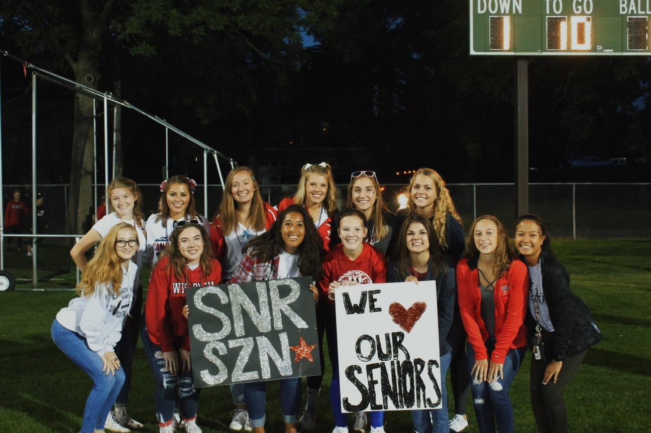 Seniors, decked out in red white and blue, Anna Giese, Macy Duden, Jada Krinke, Olivia Johnson, Kylie Wersal, Sara Twedt, Vienna Qualey, Delaney Koppmann, Kay Smith, Julia Jarvi, Emma Conway, Ellie Stodden, and Zoe Jesh cheered on the Bombers from the North end zone on September 6. This is an example of one of the first lasts for the class of 2020.