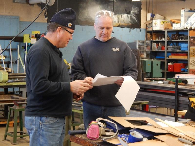 Robotics mentor Joe Coyle looks at plans for the robot with a volunteer.