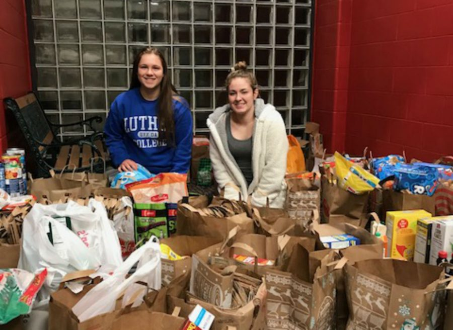 Senior%2C+Brooke+Kimmes%2C+and+junior%2C+Sophie+Epps%2C+pack+food+up+to+be+taken+to+the+food+shelf.