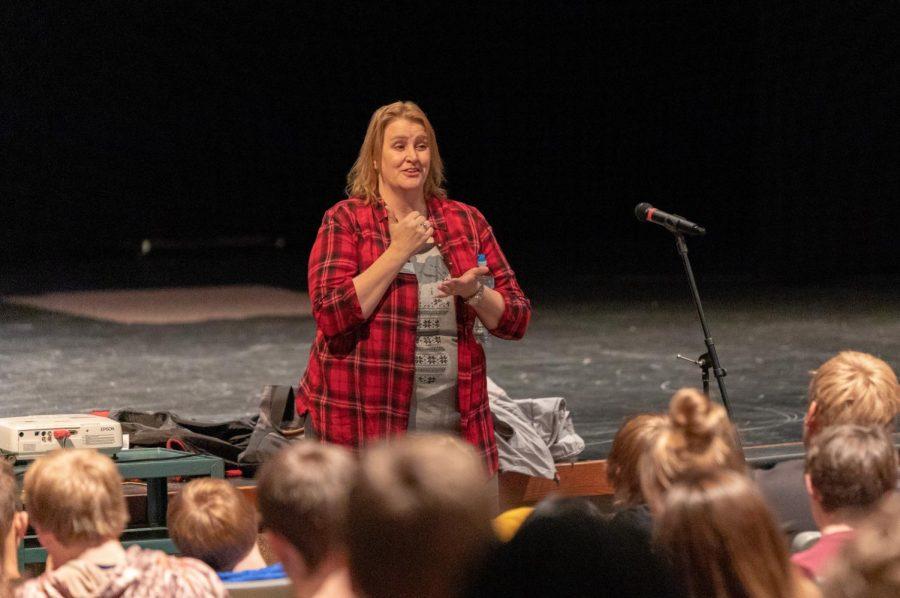 Laura Thomas addresses the junior class in the auditorium.