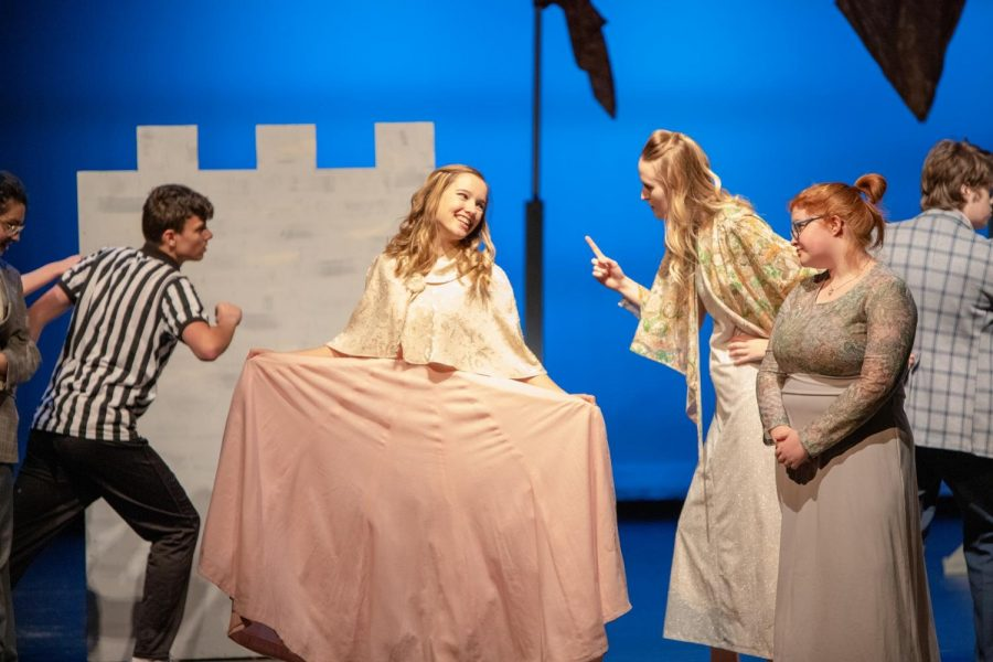 Kressin Hartl curtsies in front of Josie Ramler as the cast freezes in position on stage