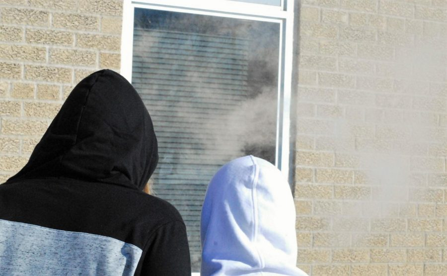 Students caught vaping outside the school building.