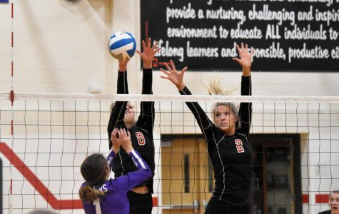 The Hustad sisters block for the Cannon Falls Bombers against the Red Wing Wingers.