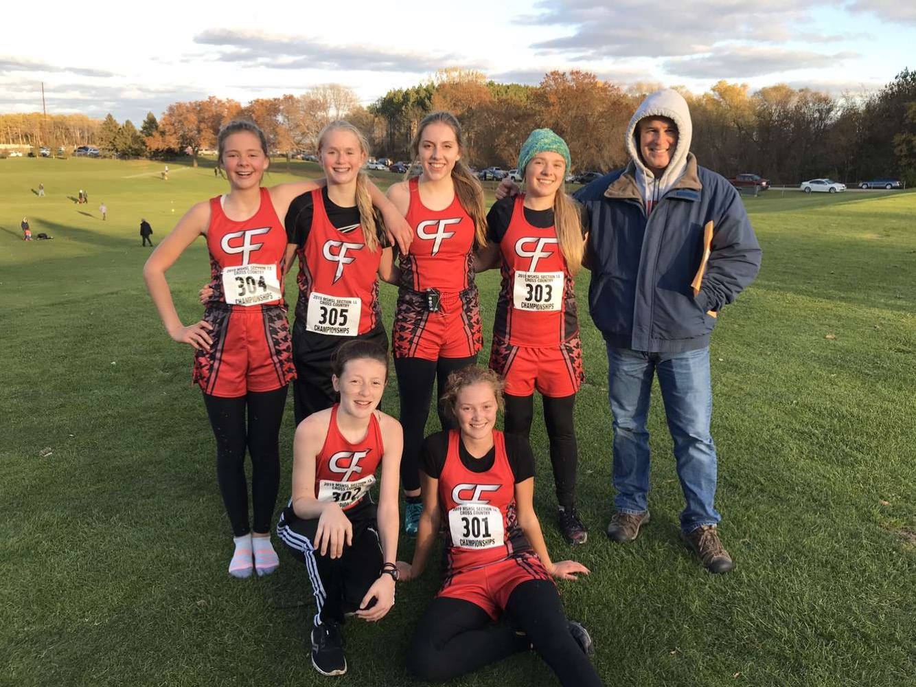 Cross Country runners pose for a photo with coach Ben Schopp after sections.