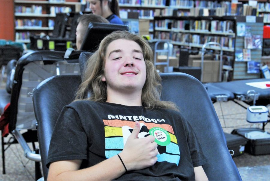 Senior Preston Heckmann gives a thumbs up for his first experience participating in a blood drive.