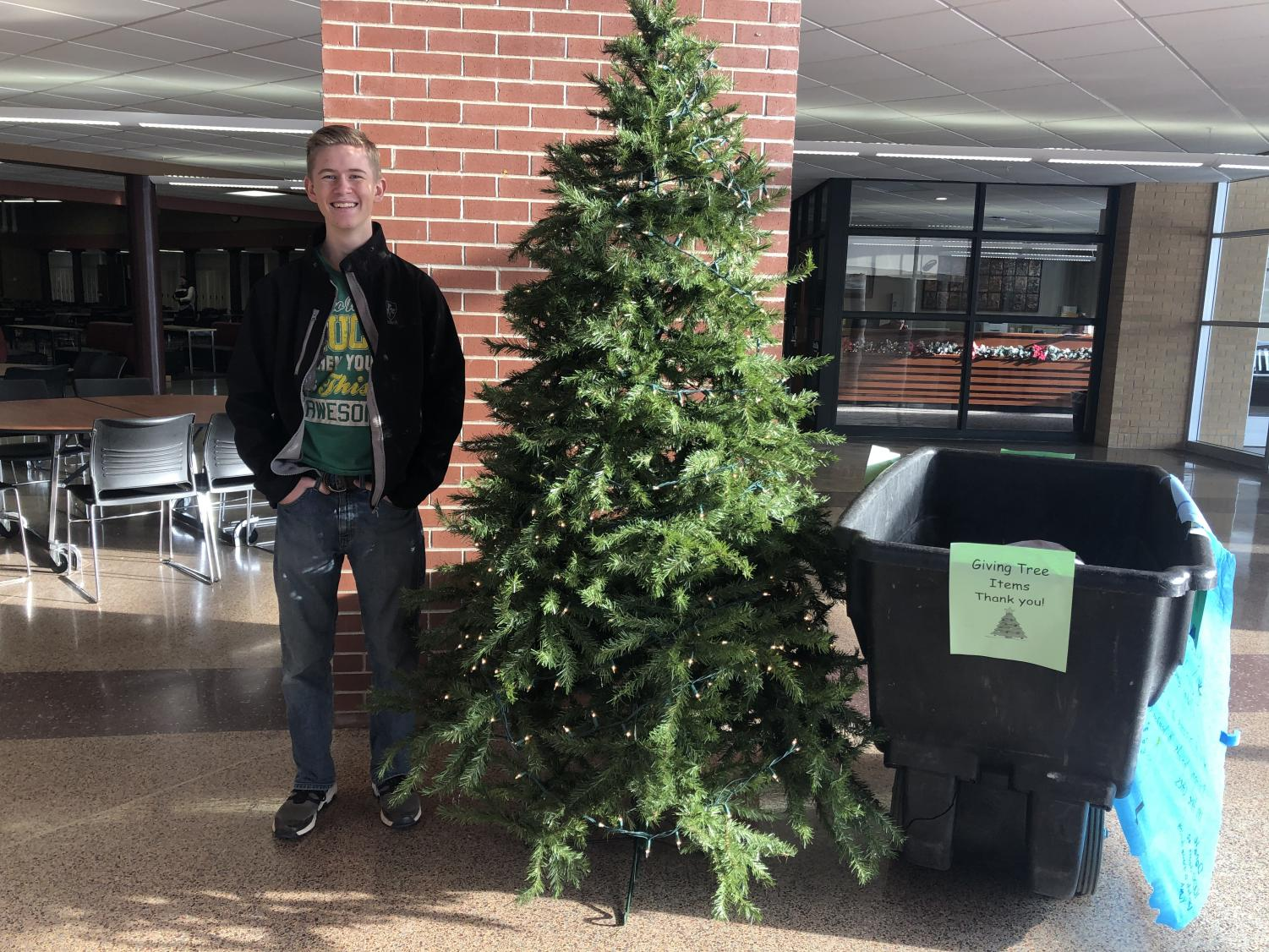 Ryan Schlichting, student  council president, poses next to the Giving Tree.