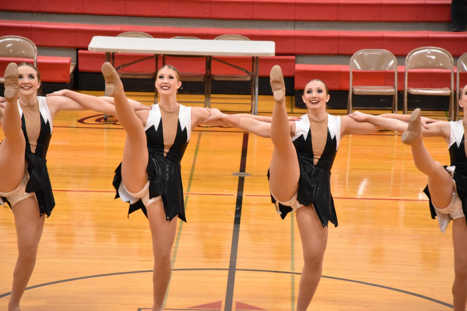 Seniors Vanessa Peer and Jada Krinke smile proudly during a kickline.