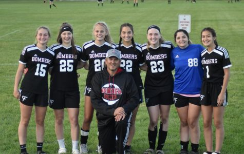 Girls' soccer seniors pose with their coach
