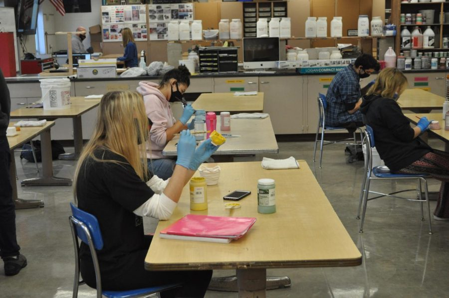 Maddie Becker works on painting a ceramics piece she created between time at school and at home.