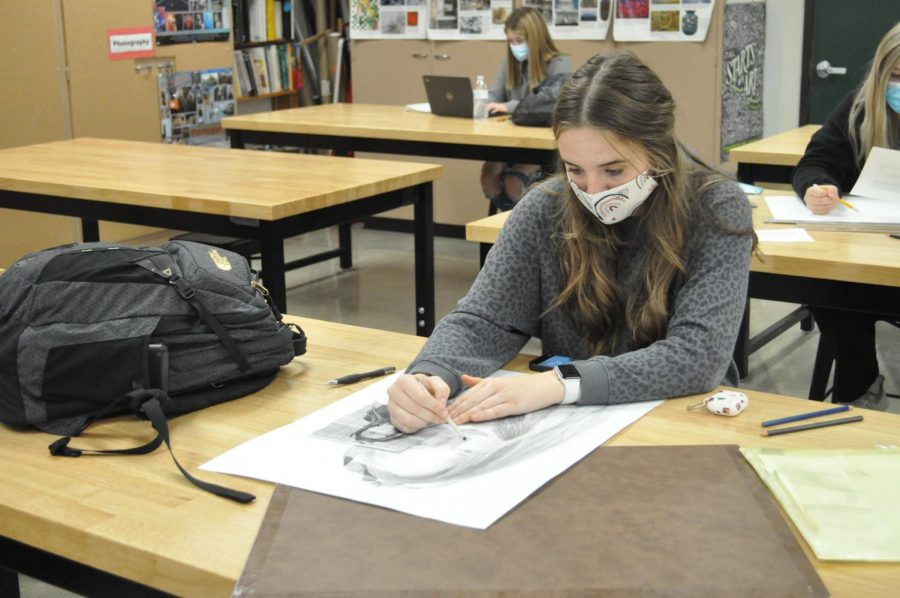 Senior Anna Becker works intensely on a portrait of one of her friends.