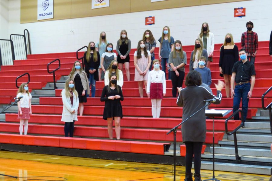 The middle school choir safely gives a performance on the gym bleachers to allow social distancing.