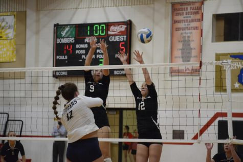 Two varsity players attempt to block an incoming hit from the Zumbrota-Mazeppa Cougars.
